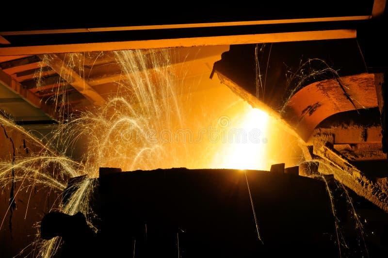 Steel furnace dumping of molten steel stock photos