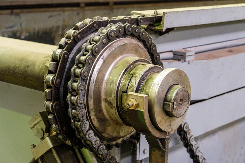 Steel gear wheel with chain drive. Steel gear wheel of industrial conveyor with chain drive royalty free stock images