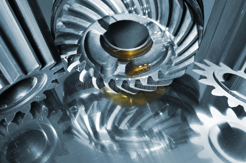 Steel gears mirrored in titanium. Large steel gears, cogs with small drips of oil, mirrored in brushed titanium, blue toning concept royalty free stock photo