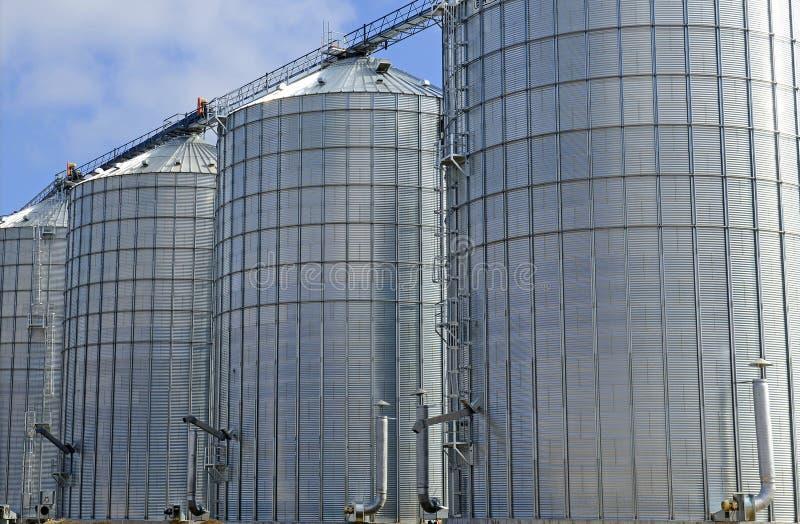 Steel grain silo on farm in rural setting stock photography
