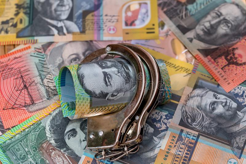 Steel handcuffs on australian dollars background close up.  stock photos