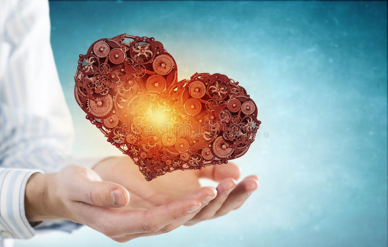 Steel heart. Businessman holding heart made of gears and cogs royalty free stock photos