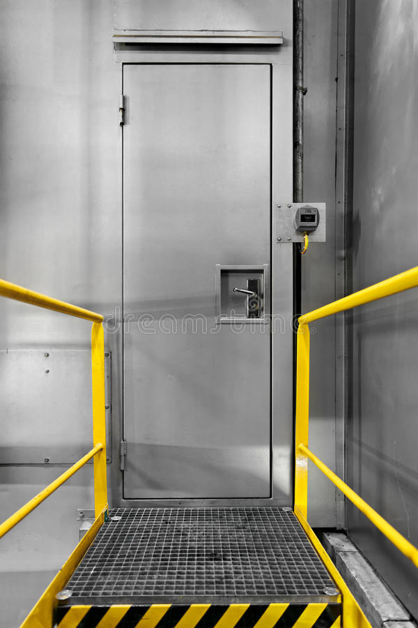 Steel industrial door with lock. And yellow frame royalty free stock photo