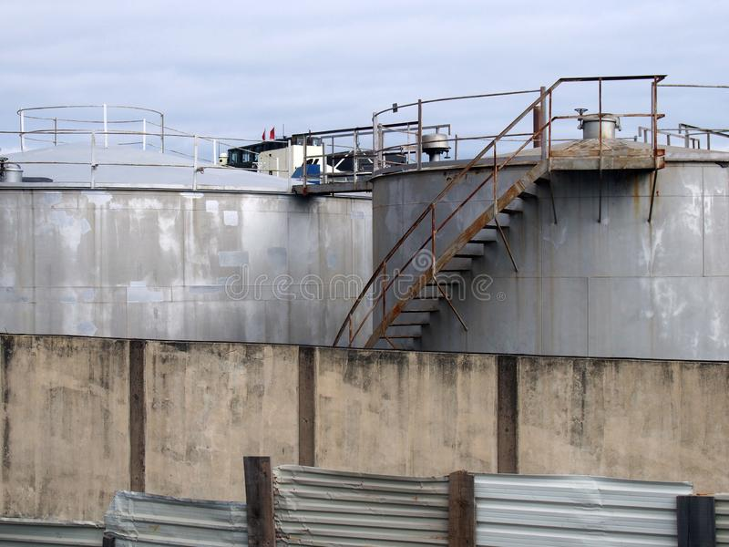 Steel industrial storage tanks with rusty stairs and walkways behind a shabby corrugated iron fence and wall stock image