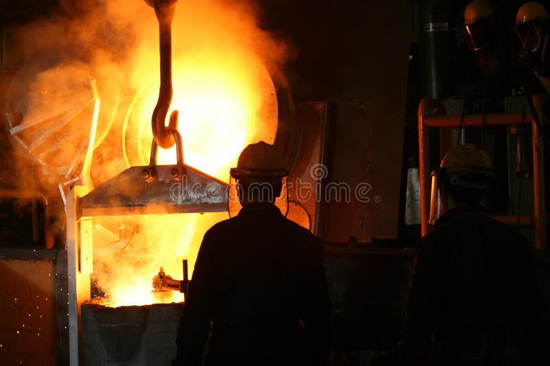 Steel Industry Molten Metal. Two foundry workmen are pouring molten metal into a large mould royalty free stock photo