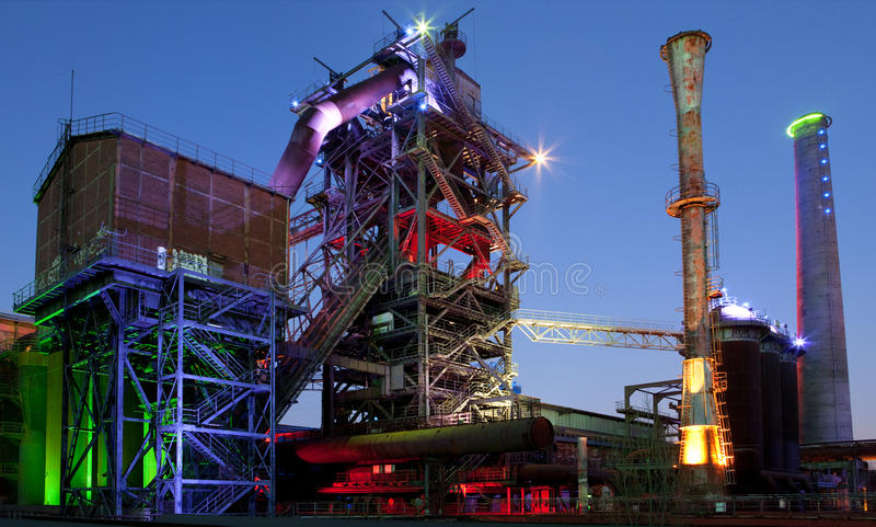 Steel industry old abandoned factory. Steel industry blast furnace factory or plant abandoned old industrial architecture at night with colored lights stock photos