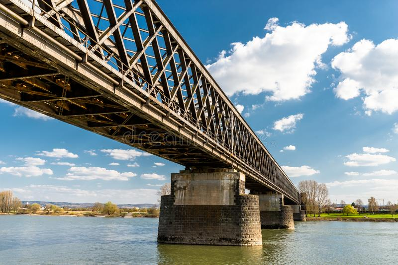 Steel, lattice structure of a railway bridge over a river with a background of blue sky with white clouds in western Germany. Steel, lattice structure of a stock image