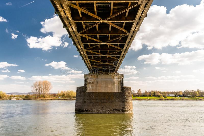 Steel, lattice structure of a railway bridge over a river with a background of blue sky with white clouds in western Germany. Steel, lattice structure of a royalty free stock images