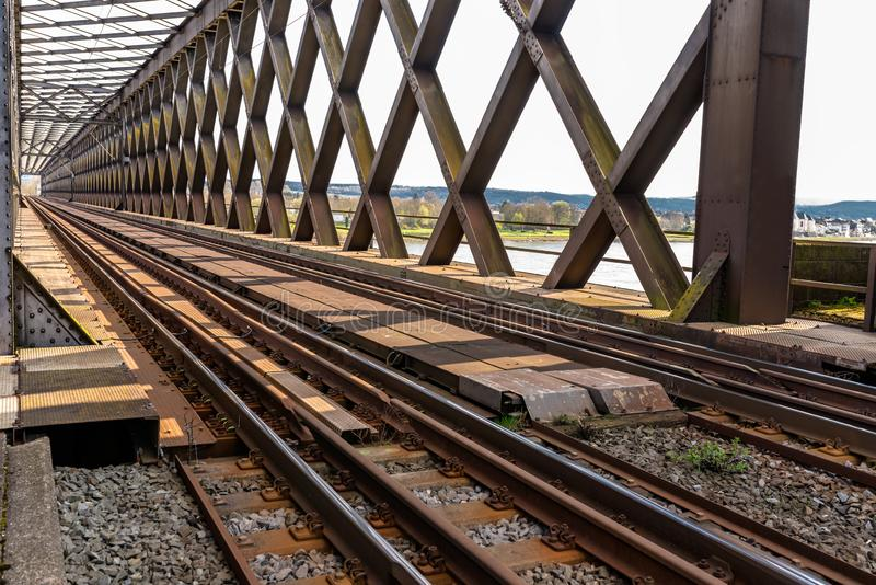 Steel, lattice structure of the railway bridge over the river, view along the tracks.  royalty free stock image