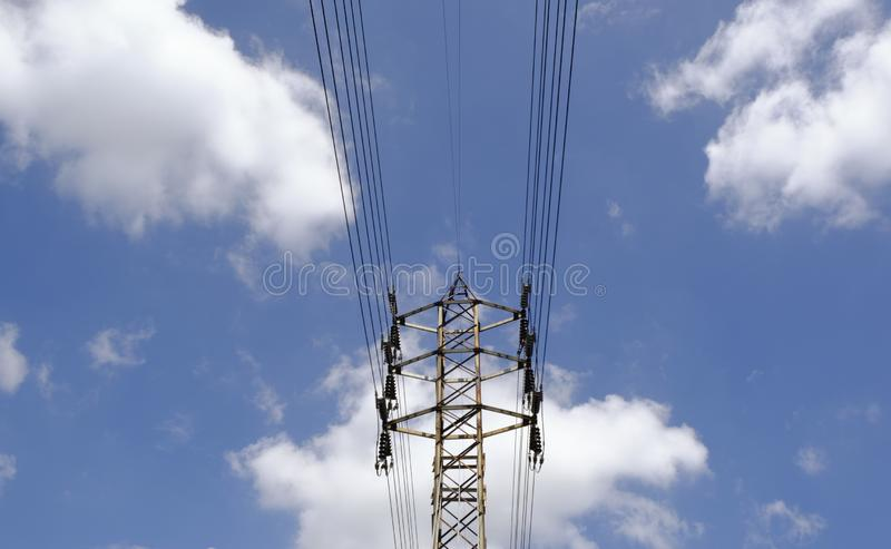 Steel lattice transmission line tower. Rises into blue sky, some white clouds stock image