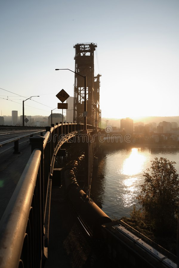 Steel lift bridge over sunbathed river into a city stock image