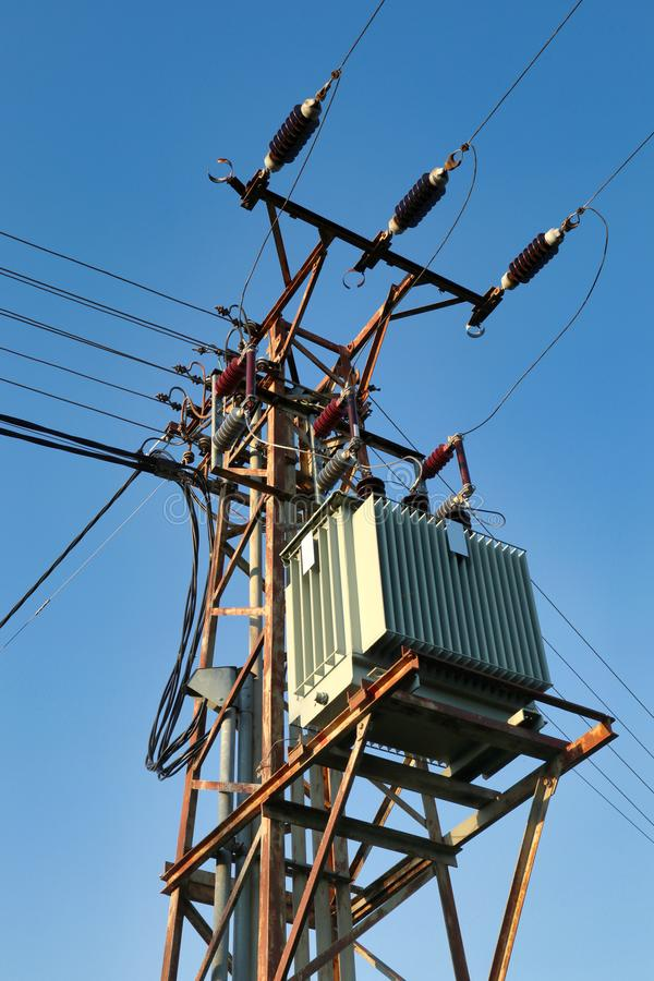 Steel mast carring high voltage powerline with distribution HV transformer royalty free stock image