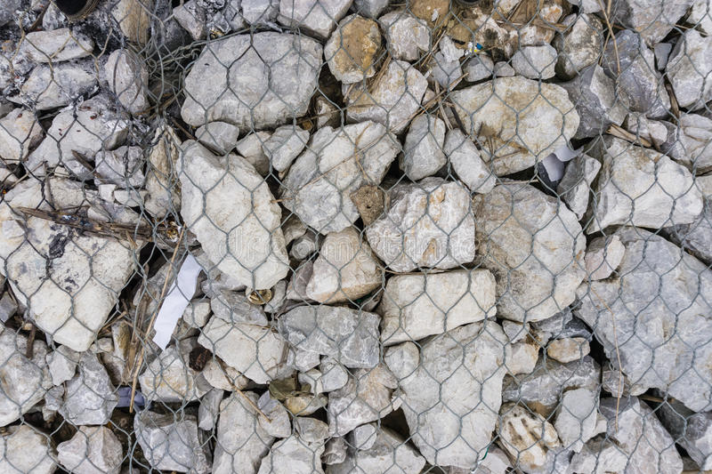 The steel mesh with gray stone stock image