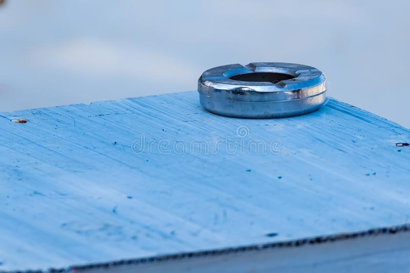 Steel metal empty ashtray on a wooden table. Background, closeup, cigarette, health, nicotine, addiction, nobody, tobacco, dirty, habit, texture, unhealthy royalty free stock photography