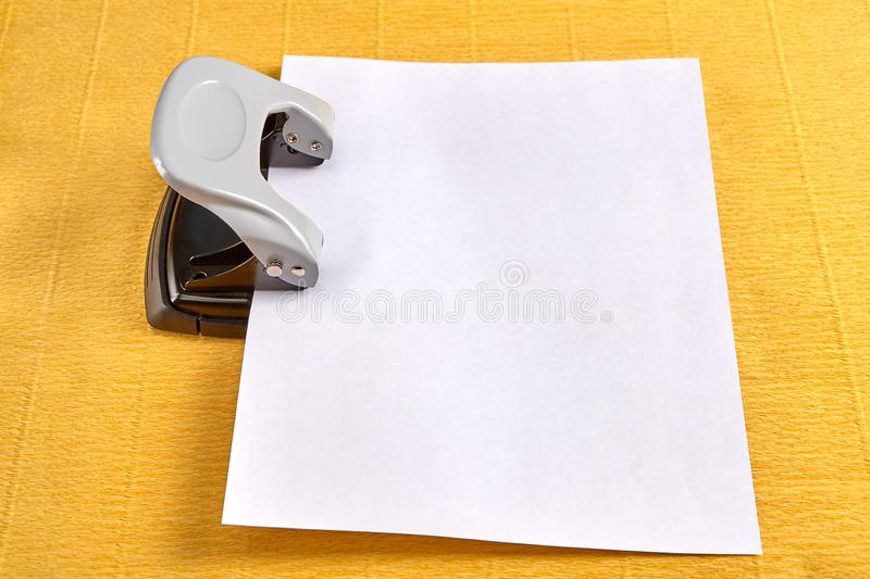 Puncher is used to perforate sheet of paper, yellow background. Steel office hole puncher is punctured by blank sheet of paper, yellow background stock photos