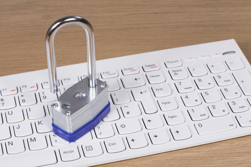 Steel padlock on a computer keyboard royalty free stock images