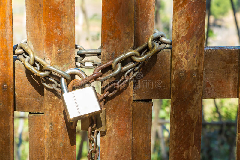 Steel padlock and rusty chain. On the wooden door royalty free stock photos