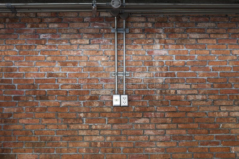 Steel pipe electric wire and plug on vintage brick wall backgrou stock photos
