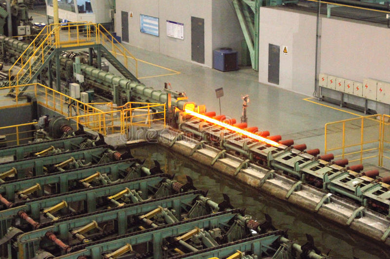 Steel pipe manufacture. The extrusion of seamless steel pipe. the red hot pipe will be quenched in the water after being extruded royalty free stock photos