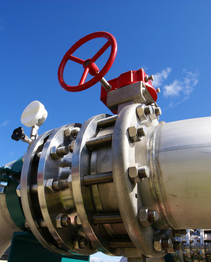 Steel pipelines and valve on blue sky stock image