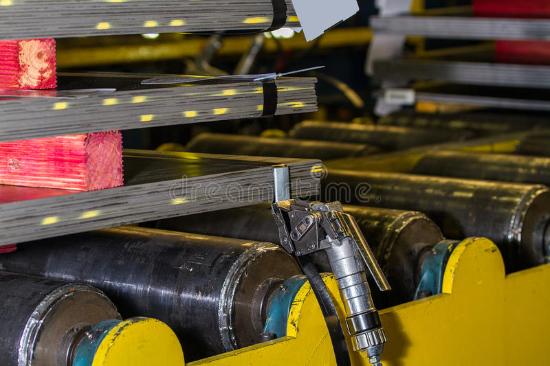 Steel plates stacked and pneumatic tensioner holding steel strap. Stacked steel plates and pneumatic tensioner holding steel strapping before pneumatic sealer royalty free stock image
