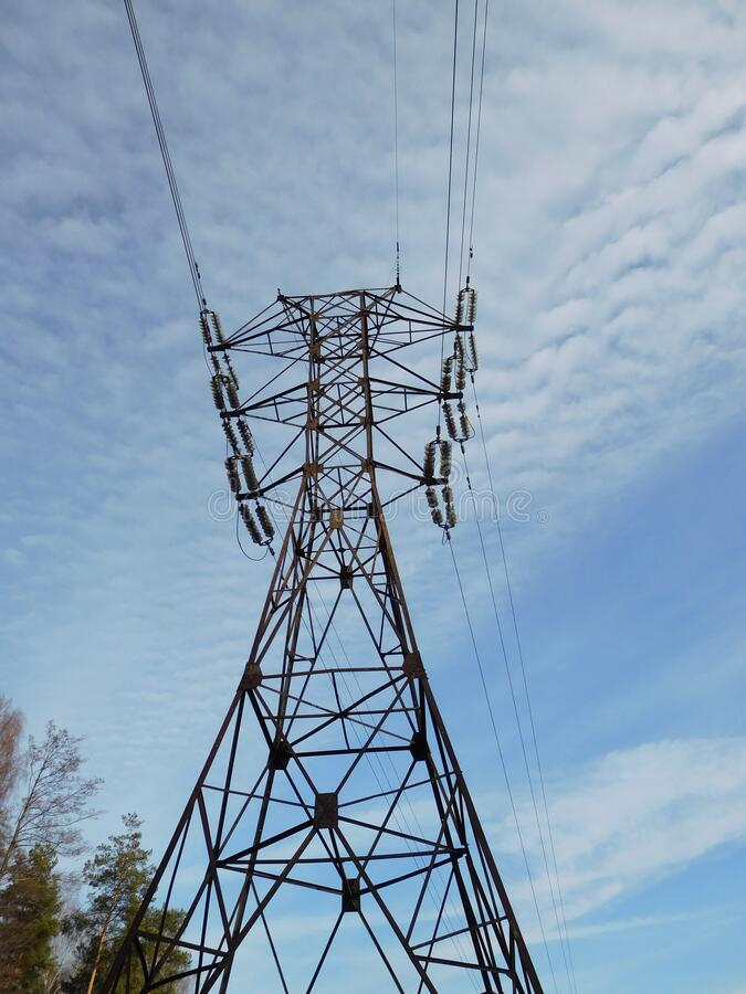 Electric pole of transmission line against a blue sky and white clouds royalty free stock photo