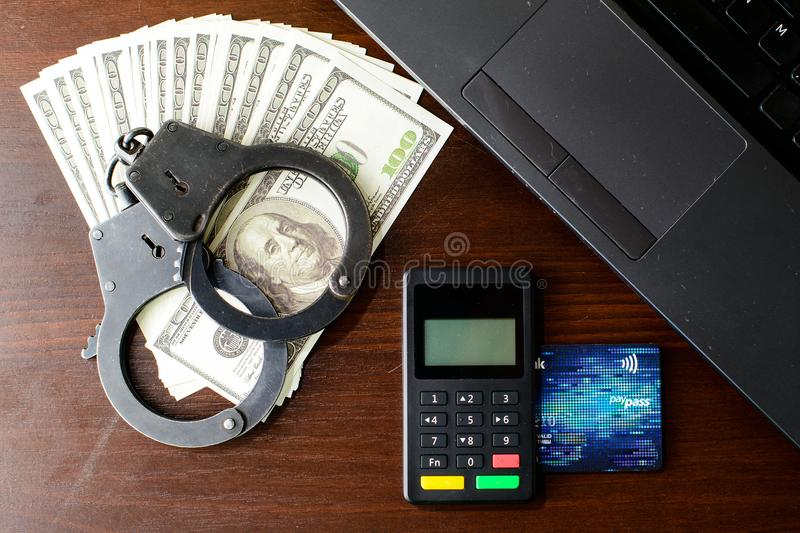 Steel police handcuffs, bank card, money dollars, payment device. And laptop lying on table, top view. Concept of internet crime, hacking, cyber crimes and royalty free stock images