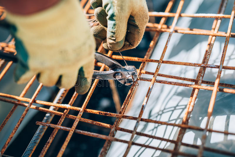 Steel reinforcement on construction site. Industrial construction worker using pliers and wire rod. Details of steel reinforcement on construction site royalty free stock image