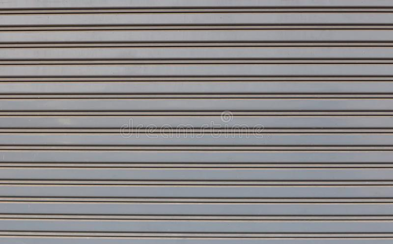 Steel rolling door of shop or store, front view. The garage door has two open handles and a keyhole. stock image