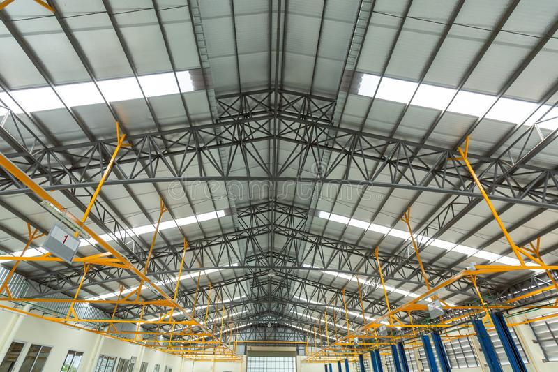Steel roof truss in car repair center, Steel roof frame Under construction, The interior of a big industrial building or factory. With steel constructions stock photography