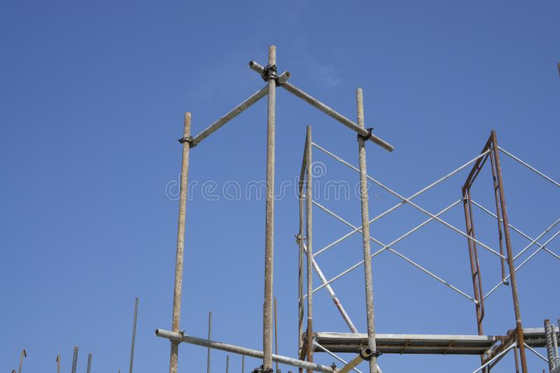 The steel scaffolding with brown rust standing on the top floor of the building under blue sky. The steel scaffolding with brown rust standing on the top floor royalty free stock photo