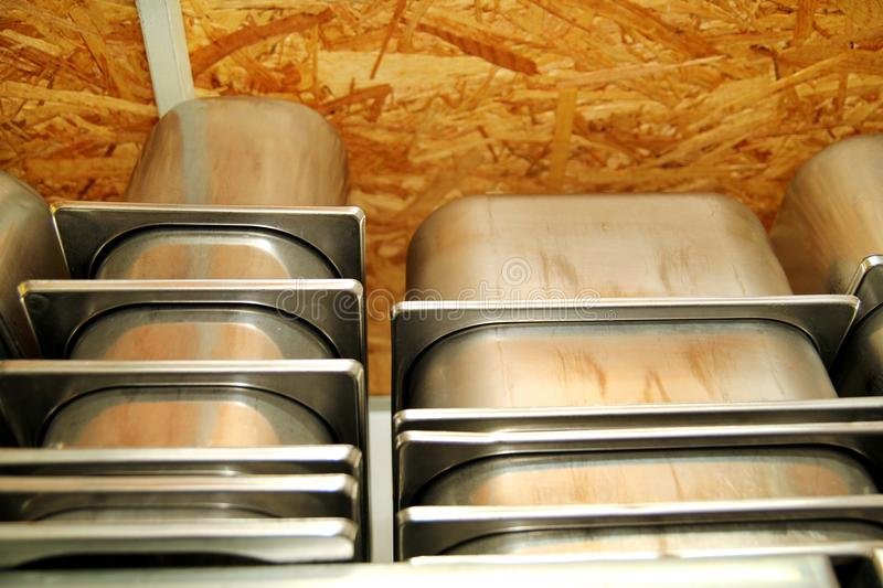 Steel service containers for ice cream packed on stacks on the shelf. Industrial preparation of creamy ice cream. Dessert, sweets. ice cream factory and pastry royalty free stock photos