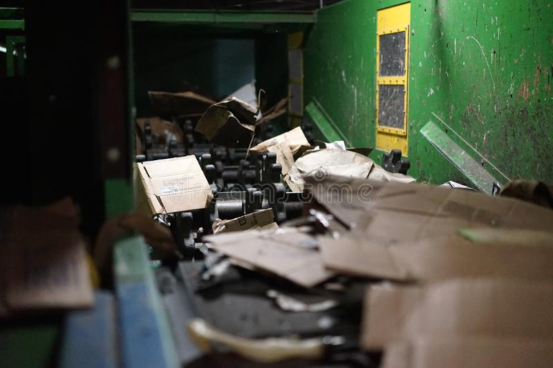 Steel shredders in cardboard recycling plant. Fierce steel shredding teeth tear cardboard into smaller pieces before packing and baling the waste feed stock photo