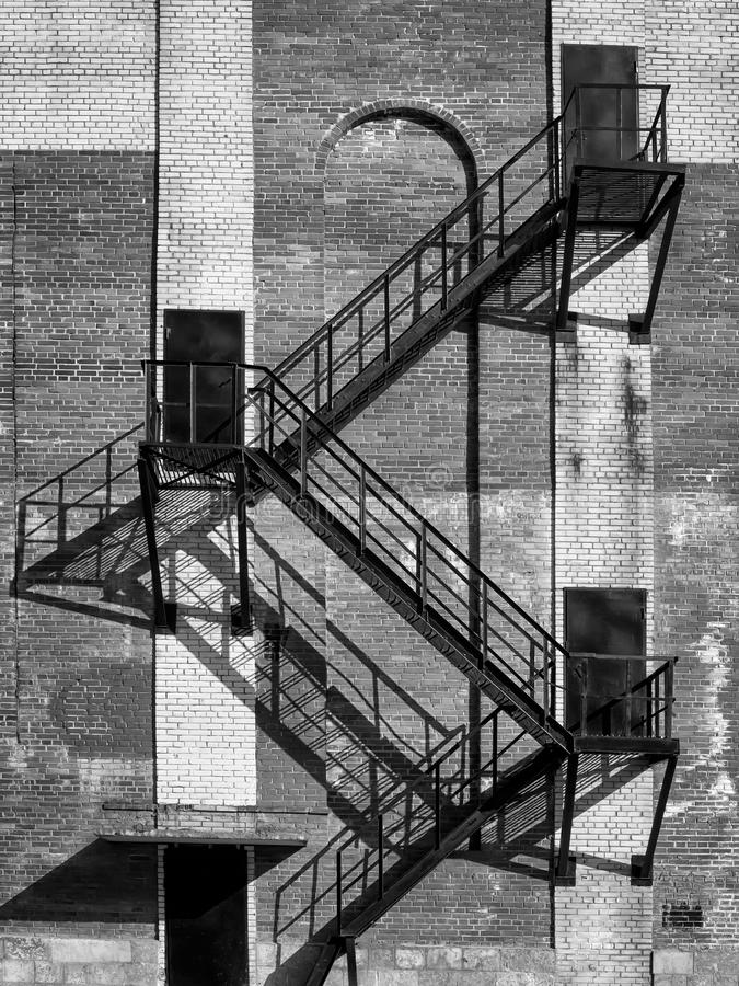 Steel stair and black doors on old industrial building brick wall. On direct hot sun. Black and white photo stock image