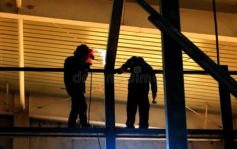 Steel structure welding. In the factory Construction site, the worker carries on the steel structure welding in the upper air stock photography