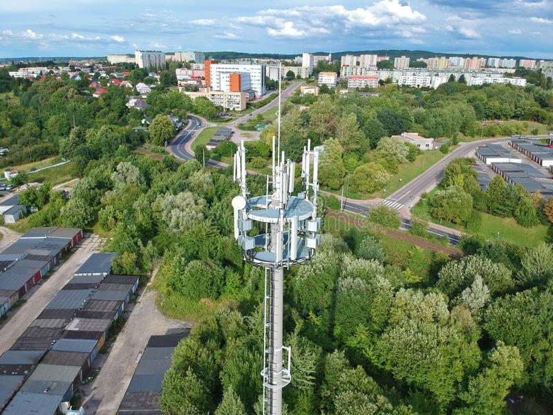 Steel telecommunication tower in the middle of city with forest, aerial view. stock photography