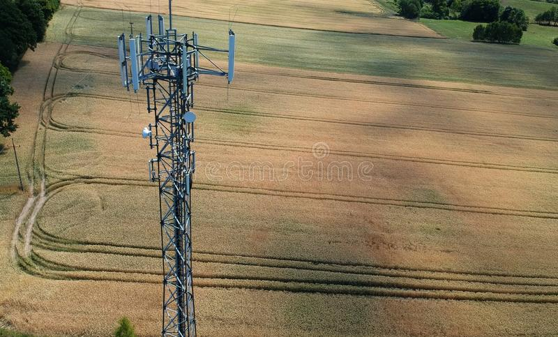 Steel telecommunication tower in the midle of wheat field, aerial view.  stock photography