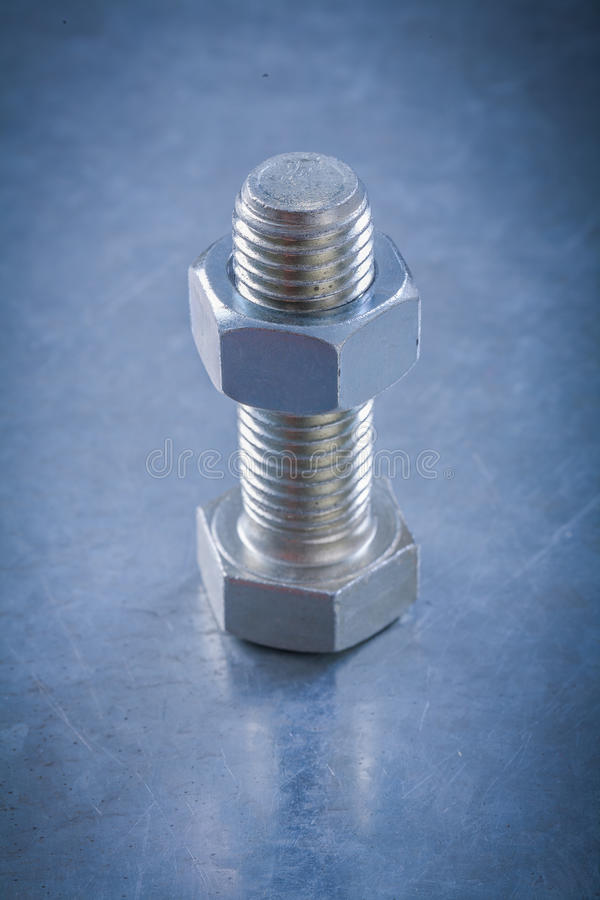 Steel threaded bolt and nut on metallic background construction. Concept stock image