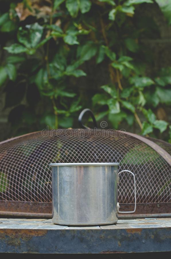 A steel tin coffee mug on the old garden table in the vines stock photo
