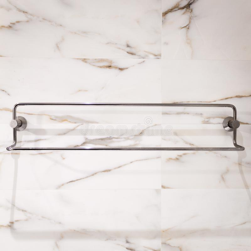 Steel Towel Rack on Marble. A bathroom towel rack in steel, on a white marble tile wall stock photography