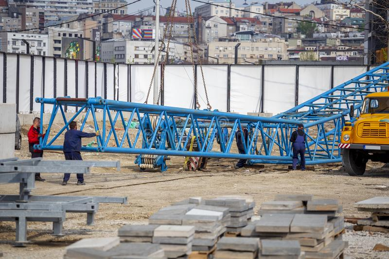 Steel tower crane installation work. BELGRADE, SERBIA - APRIL 11, 2019: Steel tower crane installation work at construction site. Erecting and assembly crane stock image