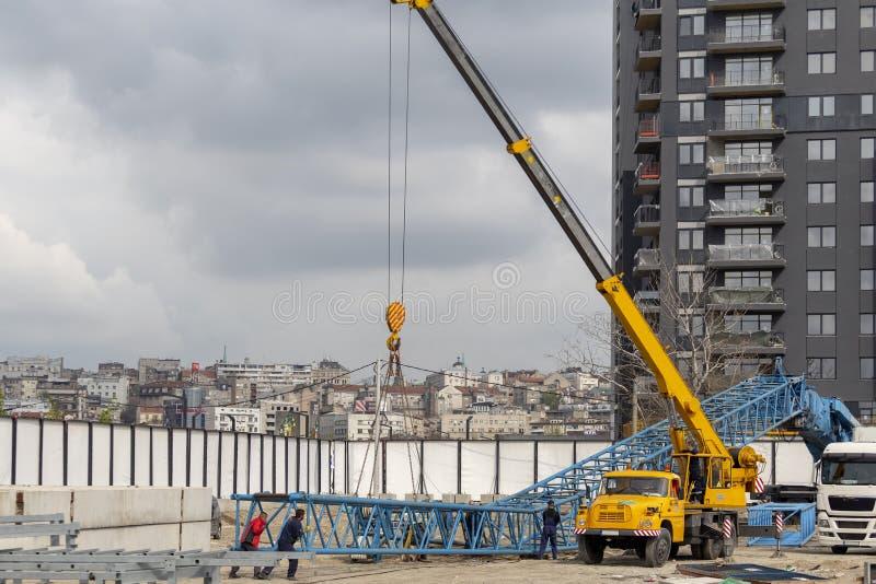 Steel tower crane installation work at construction site. BELGRADE, SERBIA - APRIL 11, 2019: Steel tower crane installation work at construction site. Erecting stock photo