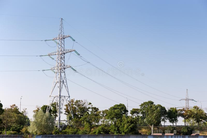 Steel transmission tower of overhead power line agains of sky. Steel lattice transmission tower of overhead power line on a background of trees and clear sky royalty free stock image