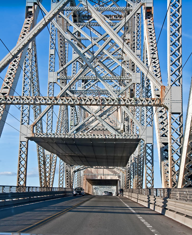 Steel Truss Bridge From Inside. This vertical traffic image is a steel truss bridge from inside the bridge perspective. Road has light traffic traveling on it in royalty free stock photo