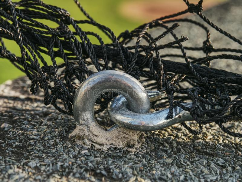 Steel twisted rope and bolt anchor eye in concrete. Steel twisted rope and steel bolt anchor eye in concrete base. The end knot of steel rope royalty free stock photography