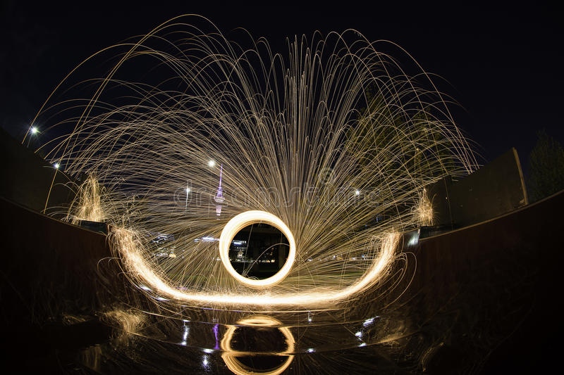 Steel wool light painting at a skate park ramp. Steel wool is set alight and spun in a circle with a long exposure. The molten metal is flung out of its cage royalty free stock photography