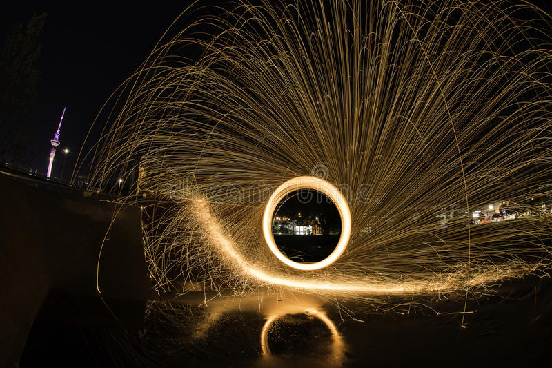 Steel wool light painting at a skate park ramp. Steel wool is set alight and spun in a circle with a long exposure. The molten metal is flung out of its cage stock images
