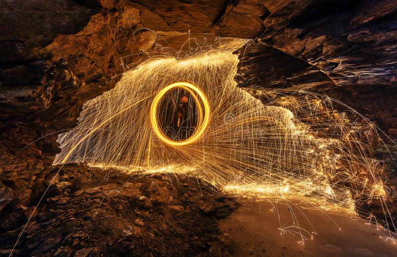 Steel wool spinning in cave. Steel wool spinning and throwing sparks all around a dark cave stock image
