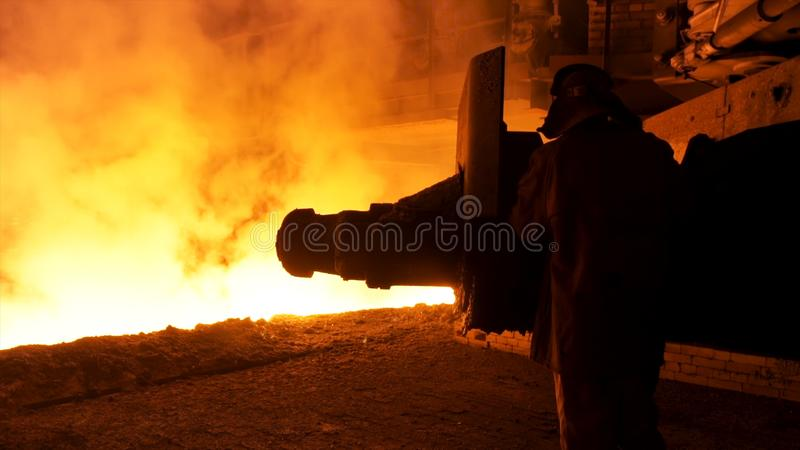 Steel worker near the molten metal flowing in the chute. Stock footage. Metallurgical equipment and technology of iron stock photo