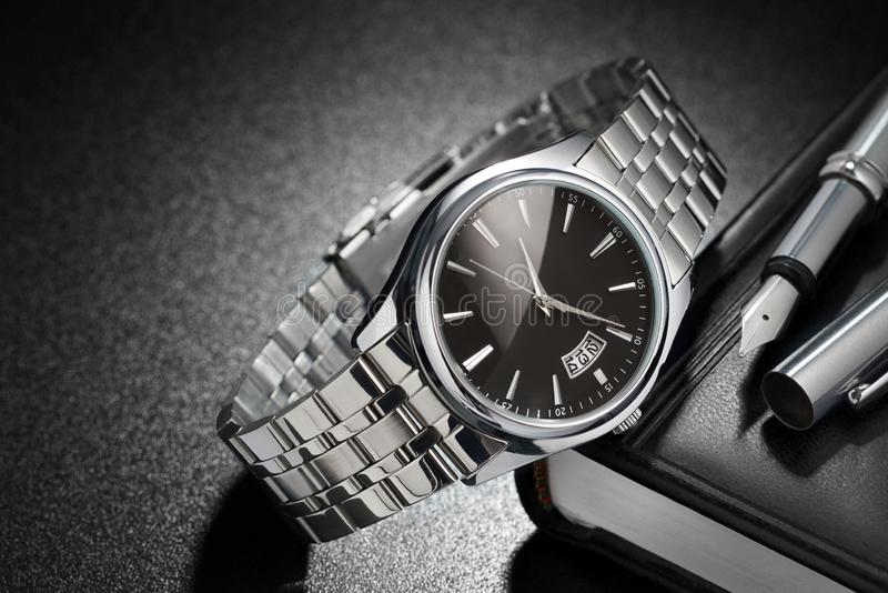 Steel wristwatch on black background stock image